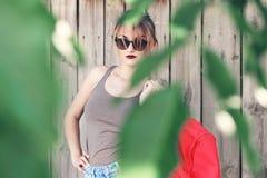 Vidros vestindo de uma menina, short da sarja de Nimes, camisa cinzenta com trouxa Fotografia de Stock Royalty Free
