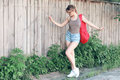 Vidros vestindo de uma menina, short da sarja de Nimes, camisa cinzenta com trouxa Foto de Stock