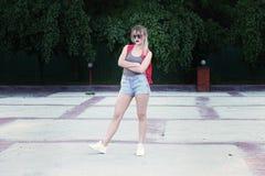 Vidros vestindo de uma menina, short da sarja de Nimes, camisa cinzenta com trouxa Imagens de Stock Royalty Free