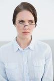 Vidros vestindo desagradados do olho da jovem mulher Fotografia de Stock