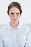Vidros vestindo desagradados do olho da mulher Foto de Stock