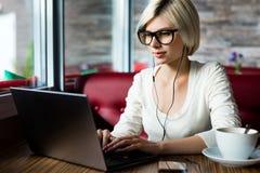 Vidros vestindo do Blogger fêmea ao usar o portátil no café imagens de stock