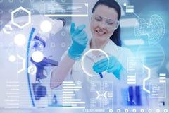 Vidros vestindo do doutor positivo ao trabalhar com tubos de ensaio e líquidos Imagens de Stock