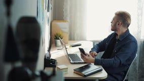Vidros vestindo do homem de negócios atrativo novo com o cabelo amarelo que trabalha em casa Usando o telefone celular que senta- vídeos de arquivo