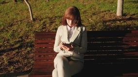 Vidros vestindo do homem de negócios fêmea bonito e trabalho com o email da tabuleta e das verificações no parque do verão em um  vídeos de arquivo