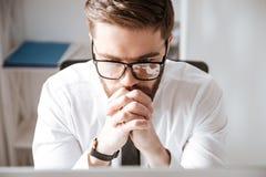 Vidros vestindo do homem de negócios novo atrativo que sentam-se no escritório Foto de Stock