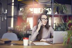 Vidros vestindo do olho da menina bonita no estúdio coworking que fala pelo smartphone Conceito dos jovens que trabalham com disp fotografia de stock