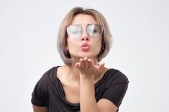 Vidros vestindo do verão da mulher bonita que enviam um beijo do ar imagem de stock royalty free