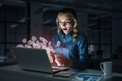 Vidros vestindo louros atrativos no escritório escuro usando o portátil M foto de stock royalty free