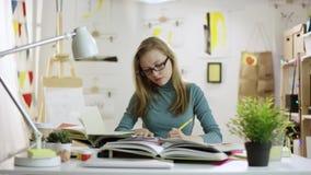 Vidros vestindo novos do estudante fêmea e trabalhos de casa fazer vídeos de arquivo