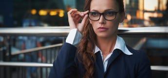 Vidros vestindo sérios da mulher de negócio imagem de stock royalty free
