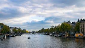 Vie di Amsterdam con la barca sull'acqua e sul cielo fotografie stock libere da diritti