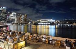 Vie nocturne animée de Sydney le long de Quay circulaire avec un grand bateau de croisière ancré dans le port Photographie stock libre de droits