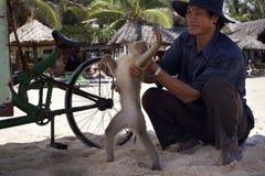 Vieatnamese en een aap op een strand stock afbeelding