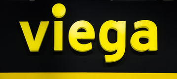 Viega company logo. Plastic yellow letters with lights on the black wall Royalty Free Stock Photography