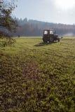 vieil agriculteur ratissant l'herbe photos stock