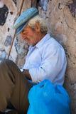 Vieil agriculteur se reposant pendant un après-midi chaud dans le village d'Oia Image stock