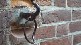 Vieil anneau en métal de rouille sur le mur avec le fond coloré de brique banque de vidéos