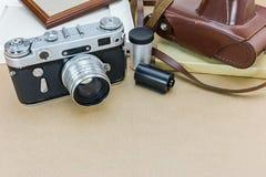 Vieil appareil-photo avec la caisse, les cadres de photo et les petits pains de film en cuir bruns Images libres de droits