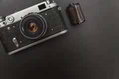 Vieil appareil-photo de film et un rouleau de film Images stock