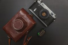 Vieil appareil-photo de film et un rouleau de film Photographie stock