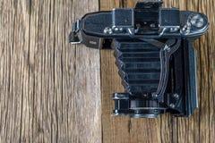 Vieil appareil-photo de pliage sur une surface en bois rustique texturisée images stock