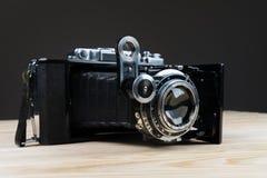 Vieil appareil-photo de pliage sur une surface en bois rustique texturisée photo stock