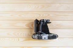 Vieil appareil-photo de pliage sur une surface en bois rustique texturisée photos libres de droits