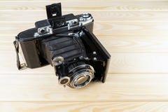 Vieil appareil-photo de pliage sur une surface en bois rustique texturisée photos stock