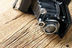 Vieil appareil-photo de pliage sur une surface en bois rustique texturisée images libres de droits