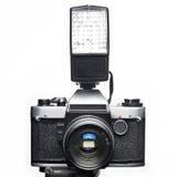 Vieil appareil-photo et éclair de SLR de film d'isolement Photographie stock libre de droits