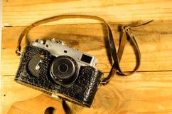 Vieil appareil-photo soviétique de télémètre dans la table en bois de l'ARO de cas en cuir photo stock