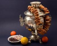 Vieil argent de samovar russe sur le fond foncé avec des mandarines de bonbons à citron de bagels photos stock