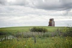 Vieil ascenseur en bois dans la distance se reposant dans un pré vert Photos libres de droits