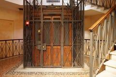 Vieil ascenseur en bois dans un axe en métal Photo stock