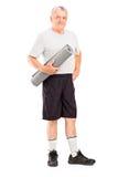 Vieil athlète retenant un couvre-tapis Photos libres de droits