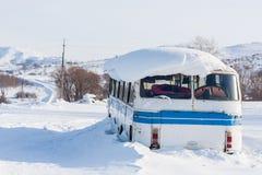 Vieil autobus de vintage couvert de neige d'hiver au fond de montagnes Photographie stock libre de droits