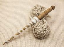 Vieil axe en bois avec une boule de fil de laine pour la fabrication des fils de laine sur un fond de tissu Photos stock