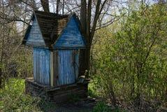 Vieil en bois bleu bien dans la cour parmi les buissons et les arbres Photo libre de droits