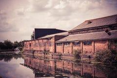 Vieil entrepôt par un canal Photos stock