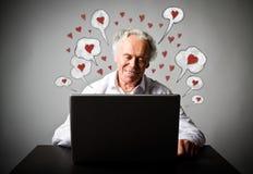 Vieil homme à l'aide d'un ordinateur portable Saint Valentin et messages romantiques d'amour Image stock