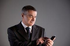 Vieil homme à l'aide d'un téléphone portable Images libres de droits