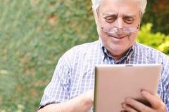 Vieil homme à l'aide du comprimé numérique Image libre de droits