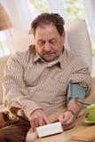 Vieil homme à l'aide du mètre de tension artérielle Photographie stock