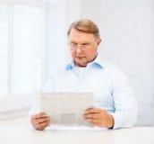 Vieil homme à la maison lisant le journal Photos stock