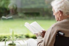 Vieil homme affichant un livre Photographie stock libre de droits