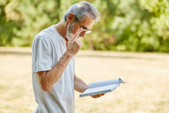 Vieil homme affichant un livre Photos libres de droits
