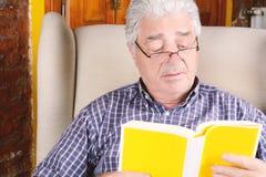 Vieil homme affichant un livre Images stock