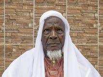 Vieil homme africain s'asseyant devant sa maison, quatre-vingts années Photographie stock