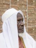 Vieil homme africain s'asseyant devant sa maison, quatre-vingts années Photographie stock libre de droits